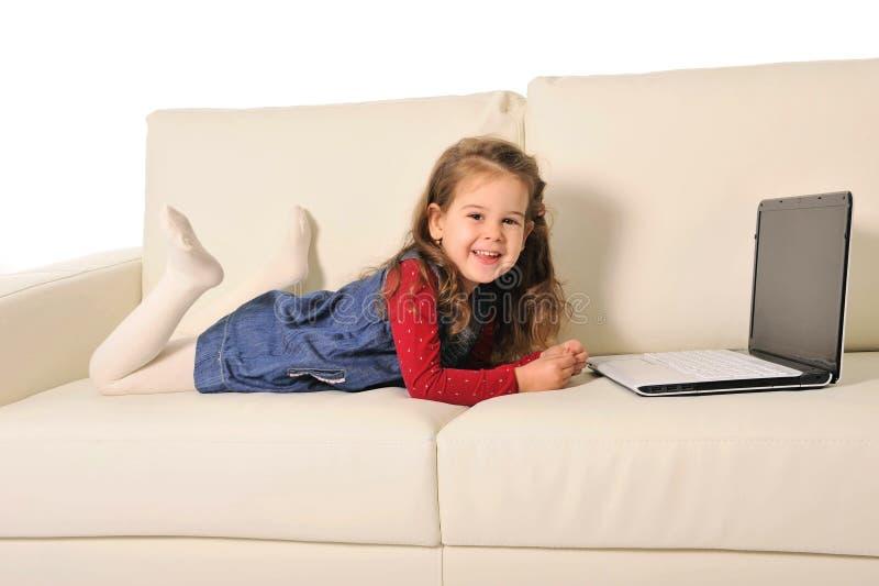 说谎在长沙发的愉快的小女孩使用与计算机 免版税库存图片