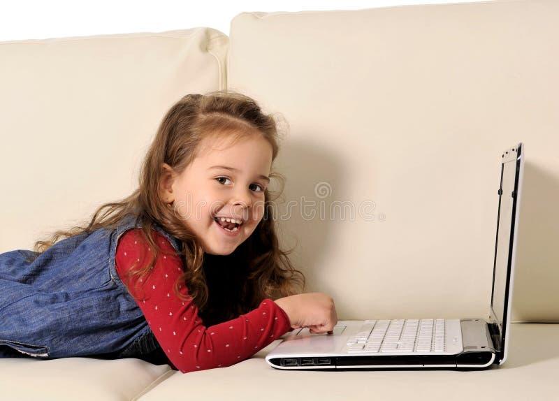 说谎在长沙发的愉快的小女孩使用与计算机 库存照片