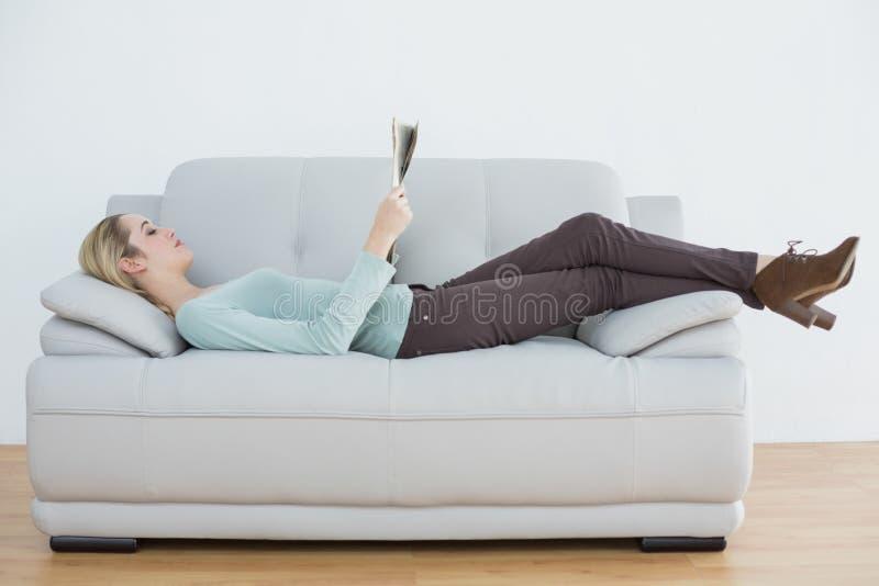 说谎在长沙发的有吸引力的白肤金发的妇女读书报纸 免版税库存图片