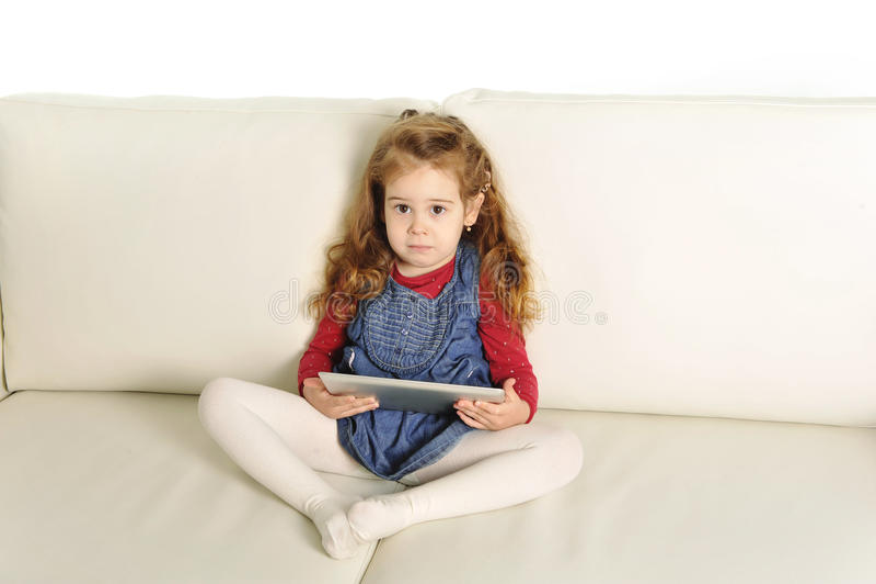说谎在长沙发的甜小女孩使用与数字式垫 库存图片