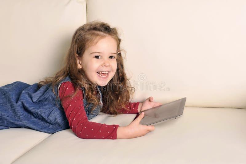 说谎在长沙发的甜小女孩使用与数字式垫 免版税库存照片