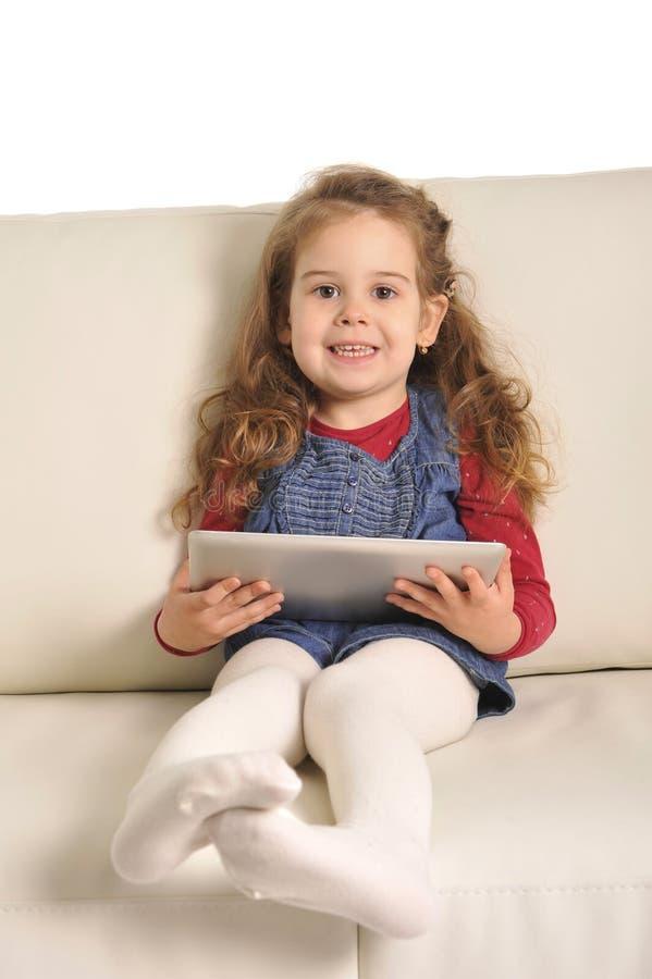 说谎在长沙发的甜小女孩使用与数字式垫 免版税库存图片