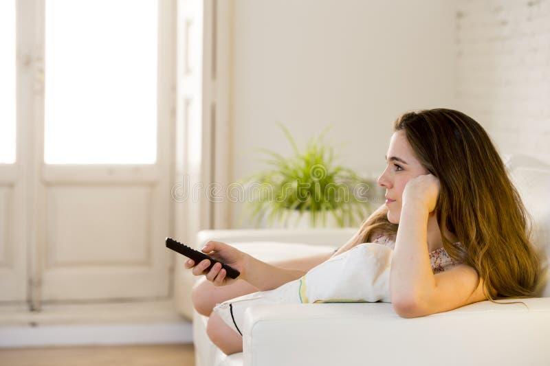 说谎在长沙发的年轻美丽的妇女拿着遥控观看的电视愉快和轻松 免版税库存照片