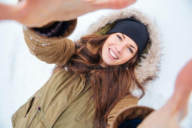 说谎在雪和采取的微笑的妇女selfie 免版税库存图片