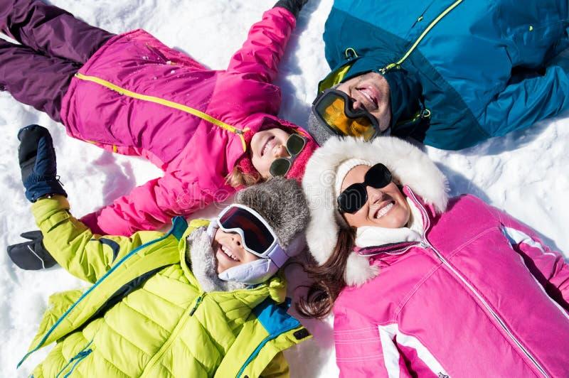 说谎在雪的微笑的家庭 免版税图库摄影
