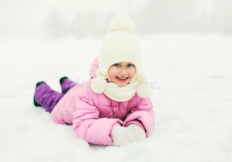 说谎在雪的愉快的微笑的小女孩孩子在冬天 库存照片