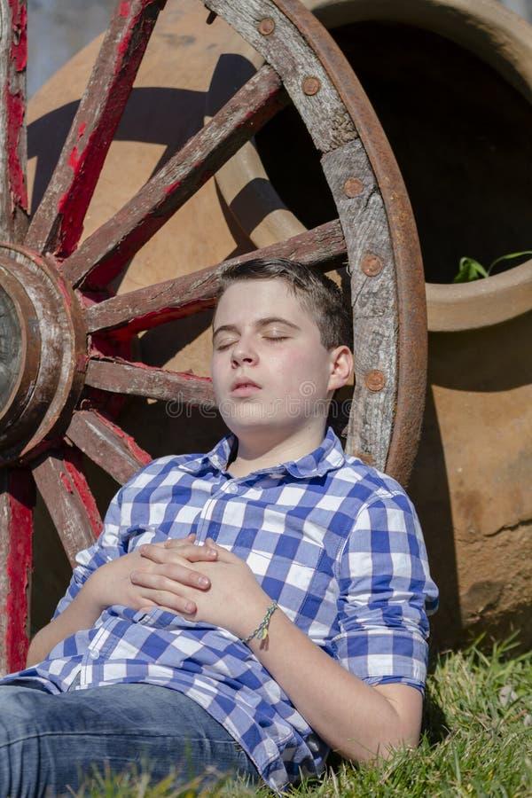 说谎在马车车轮旁边的年轻牛仔 免版税图库摄影