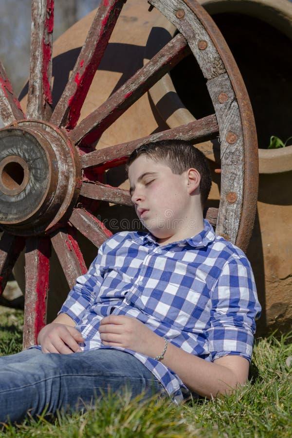 说谎在马车车轮旁边的年轻牛仔 库存照片