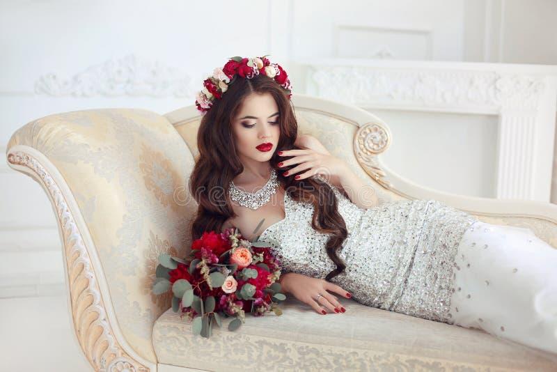 说谎在经典典雅的沙发的美丽的深色的新娘,巴洛克式 库存照片