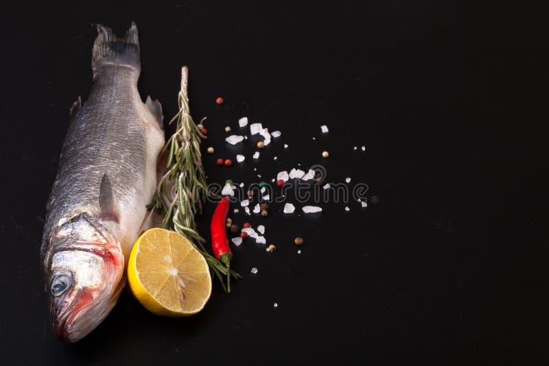 说谎在黑暗的背景的新鲜的海鱼用香料 t的空间 免版税库存照片