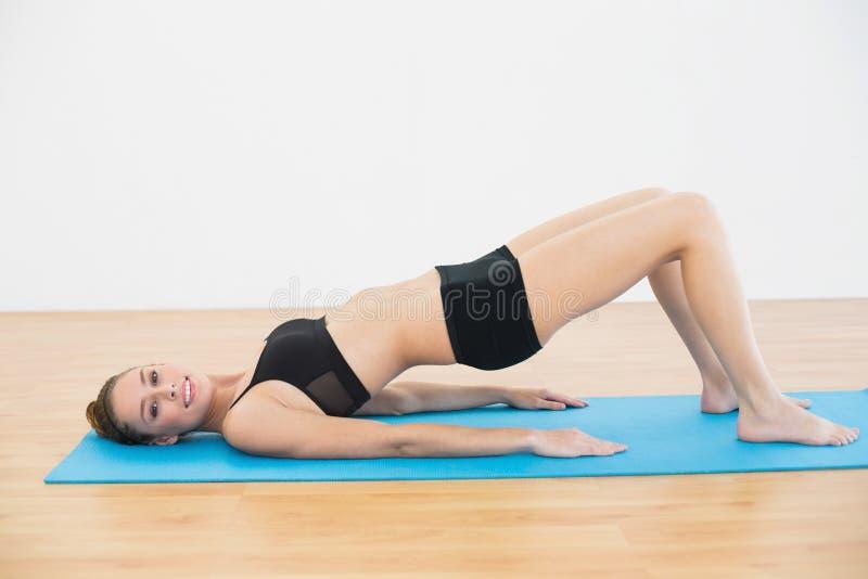 说谎在锻炼席子的运动服的高兴的少妇做锻炼 免版税图库摄影
