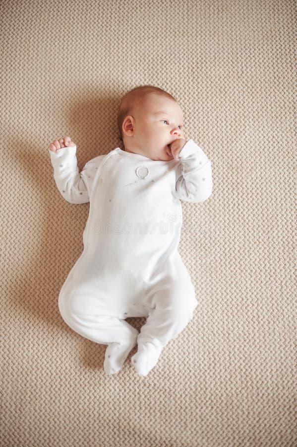 说谎在他的后面和候宰栏的白色睡衣的俏丽的婴孩在嘴 库存图片