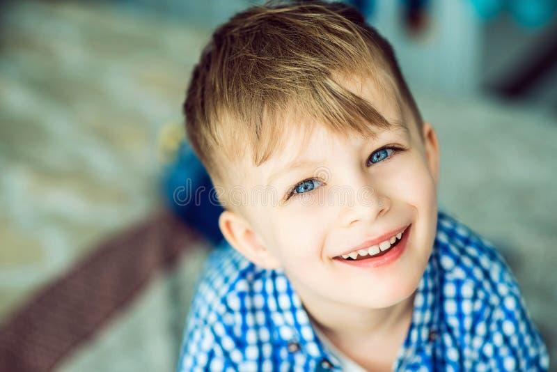 说谎在他的父母的床上的一个蓝眼睛的矮小的微笑的男孩的画象 库存图片
