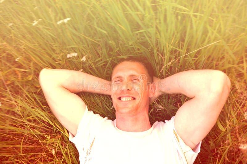 说谎在绿色夏天草的人 免版税图库摄影