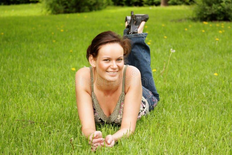 说谎在绿色草坪的少妇 库存照片