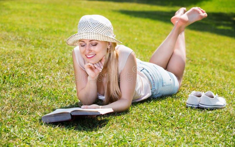 说谎在绿色草坪的l妇女画象在公园和阅读书 免版税库存图片