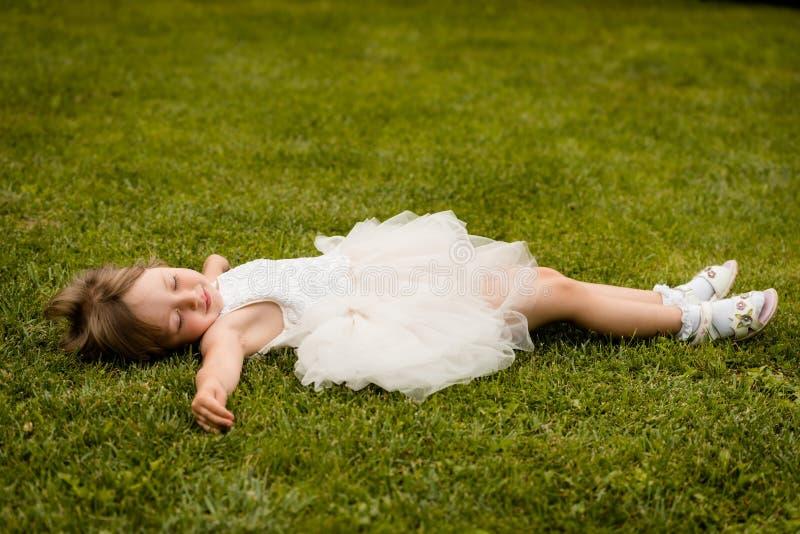说谎在绿色草甸的白色礼服的女孩孩子 免版税库存照片
