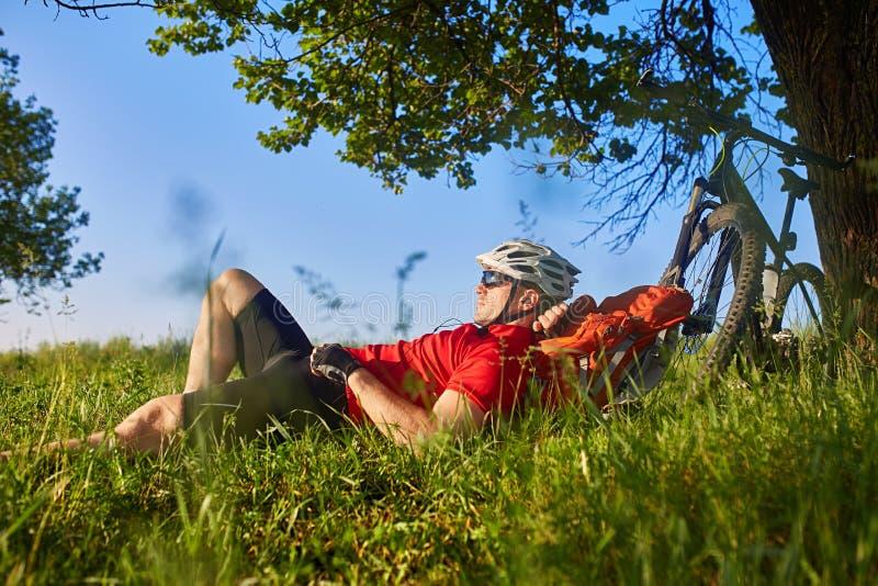 说谎在绿色草甸的英俊的年轻人夏天画象在自行车和背包附近 库存照片