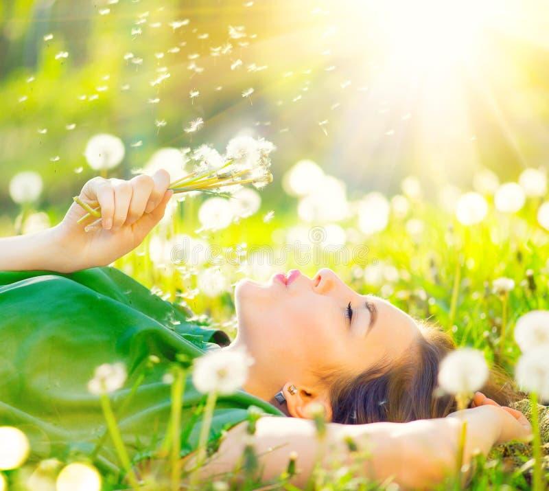 说谎在绿草和吹的蒲公英的领域的美丽的妇女 库存图片