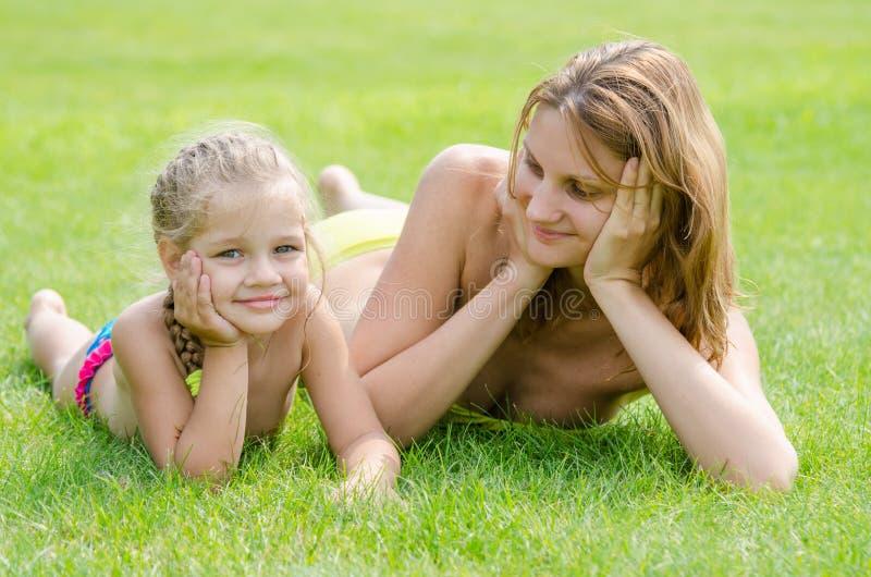 说谎在绿草和看他的五年女儿的年轻母亲在附近说谎 库存照片