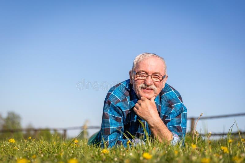 说谎在绿草的夏天领域的老人 免版税库存图片