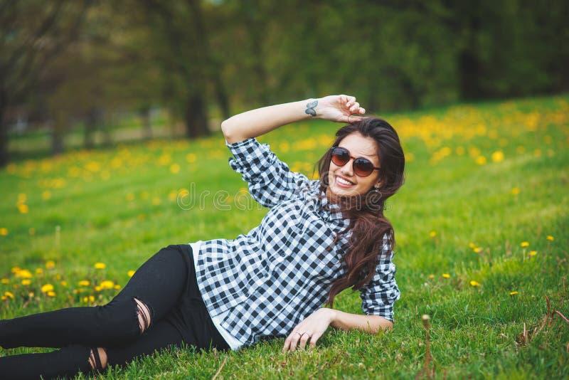 说谎在绿草的格子花呢上衣和太阳镜的时髦的女孩在春天 免版税库存图片