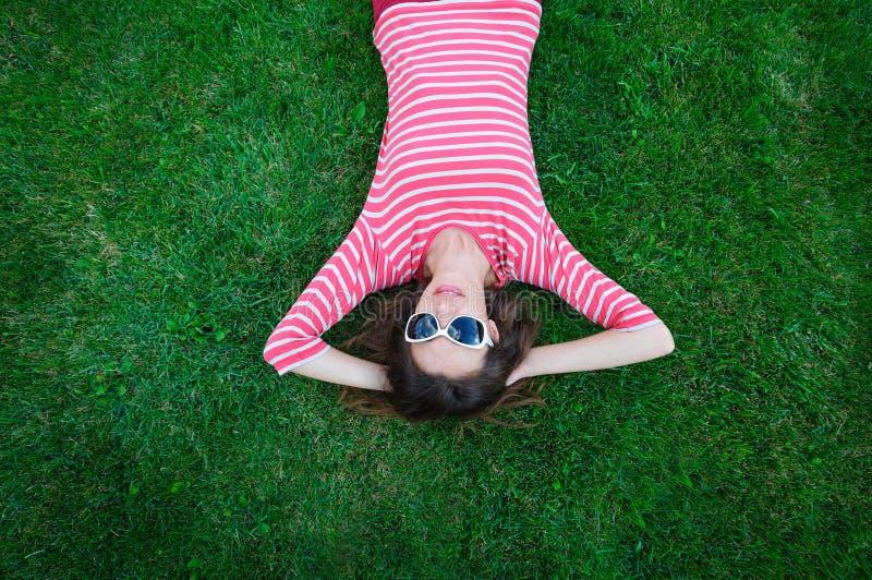 说谎在绿草的美丽的少妇在草甸 免版税库存图片