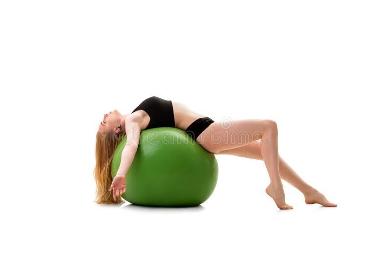 说谎女性的体操运动员在绿色大fitball支持 免版税库存图片