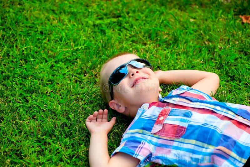 说谎愉快的小男孩下来基于绿草 库存照片