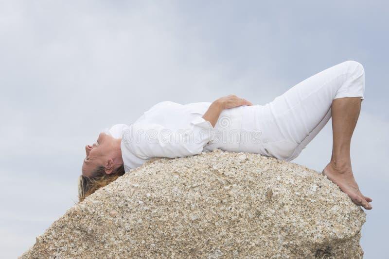 说谎的妇女放松在室外的岩石顶部 免版税图库摄影