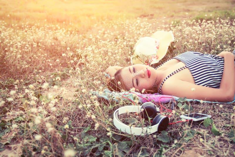 说谎美丽的性感的少妇临近在花的耳机 免版税图库摄影