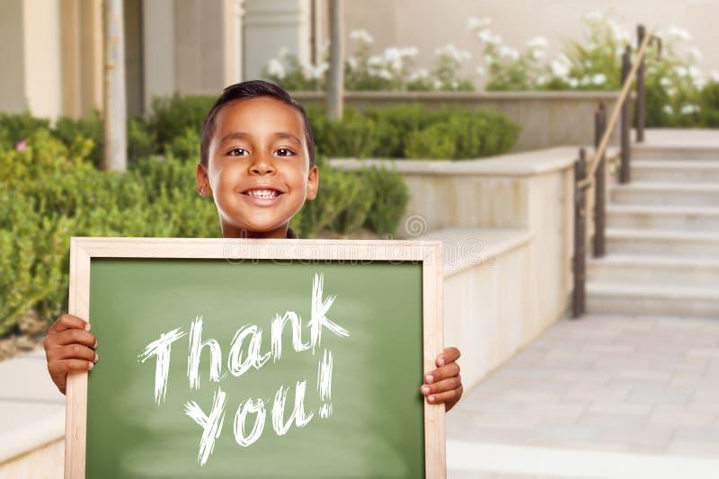 谢谢在学校校园里的西班牙男孩举行的粉笔板 免版税库存照片