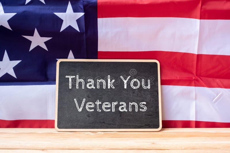 谢谢在有美利坚合众国的旗子的黑板写的退伍军人文本在木背景 库存照片