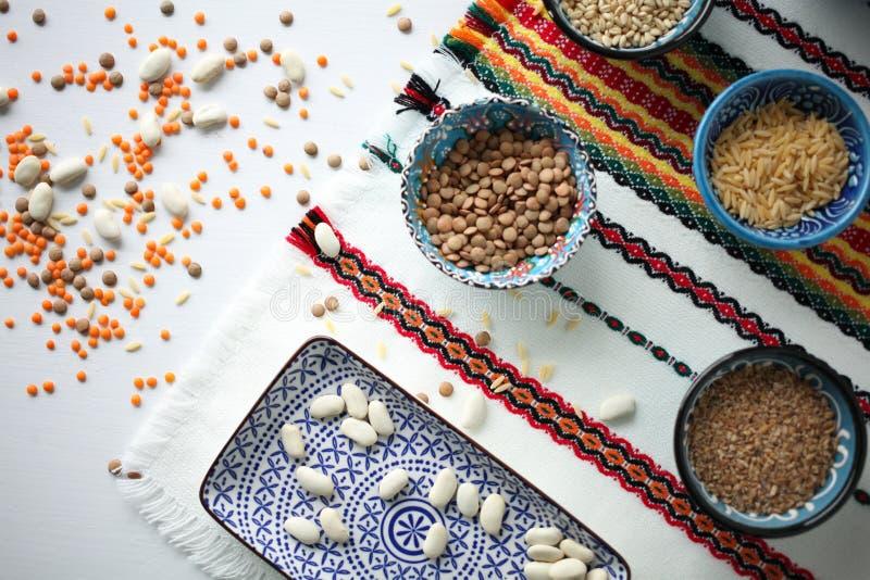 谷物、豆和扁豆的分类在传统土耳其陶瓷碗在明亮的桌布 库存图片