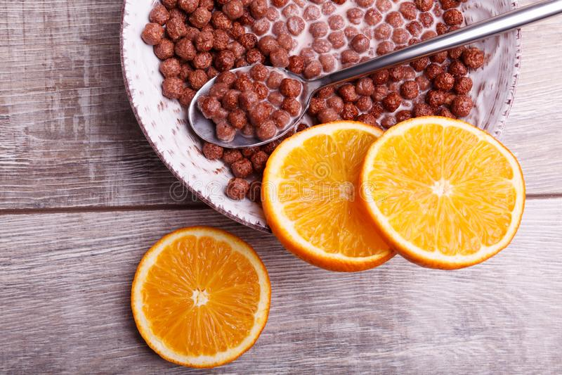 谷物在碗的巧克力球用牛奶 在桌上的被切的柑橘 库存图片