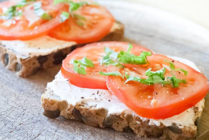 谷物面包切片用蕃茄和乳清干酪 库存照片