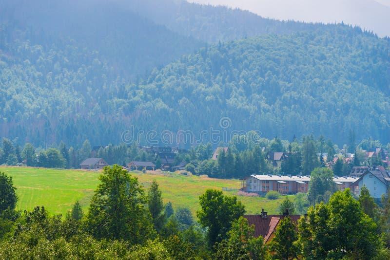 谷的村庄在被围拢的山的脚  库存照片
