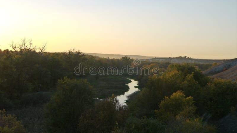 谷的河反对日落秋天太阳的背景 库存图片