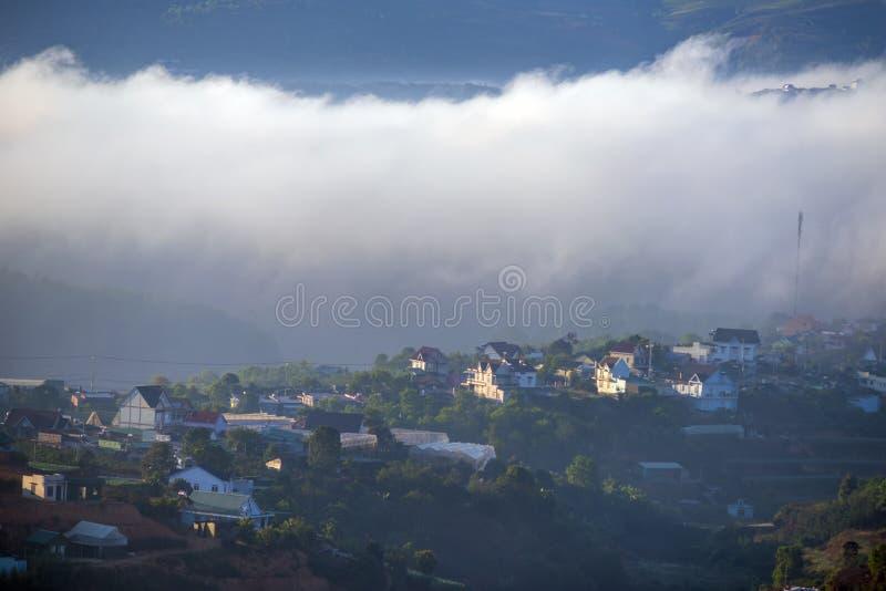 谷的美丽的雾盖子村庄与作为海岛的五颜六色的房子薄雾的第2部分 免版税库存照片