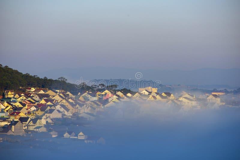 谷的美丽的雾盖子村庄与作为海岛的五颜六色的房子薄雾的 库存图片
