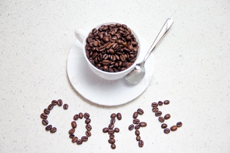 豆咖啡杯白色 分散的咖啡豆 库存照片