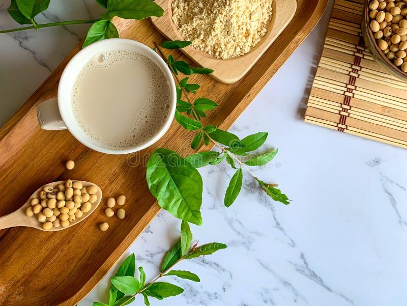豆奶杯子、大豆种子在木匙子和豆奶粉末顶视图在一块木板材 免版税库存图片