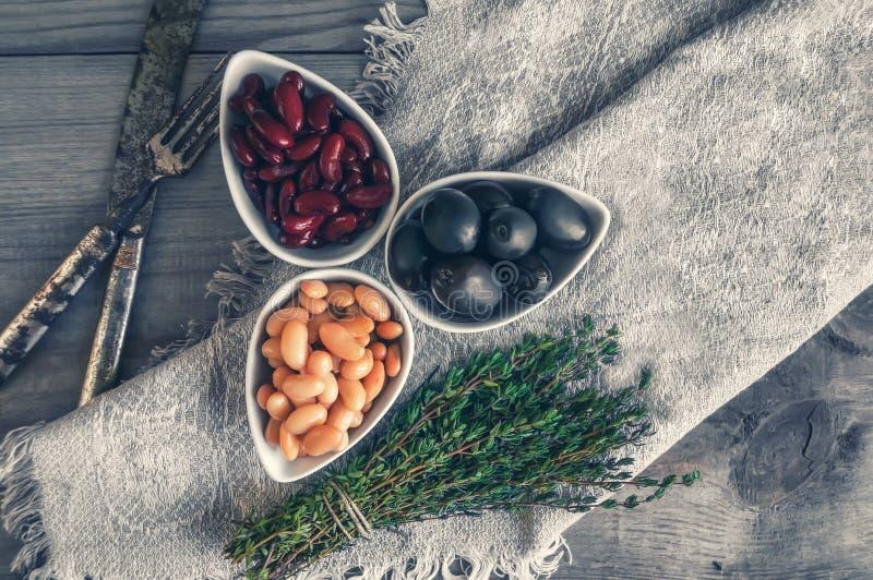 豆白色和红色用在白色小碗的大黑橄榄为沙拉做准备用麝香草 关闭 库存照片