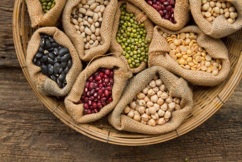 豆类在大袋袋子的种子豆在木背景 库存照片