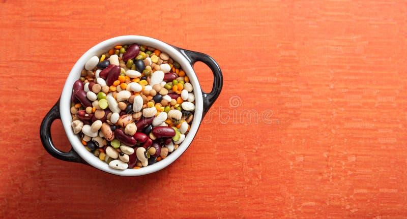 豆类的分类在上釉的碗的在橙色背景,被隔绝的,顶视图,拷贝空间 免版税库存照片