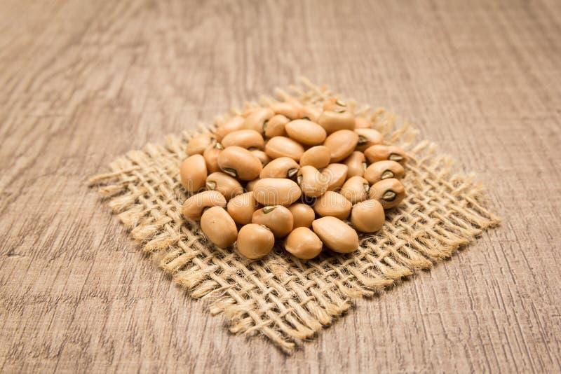 豇豆豆类 在黄麻方形的保险开关的五谷  木的表 Se 库存图片