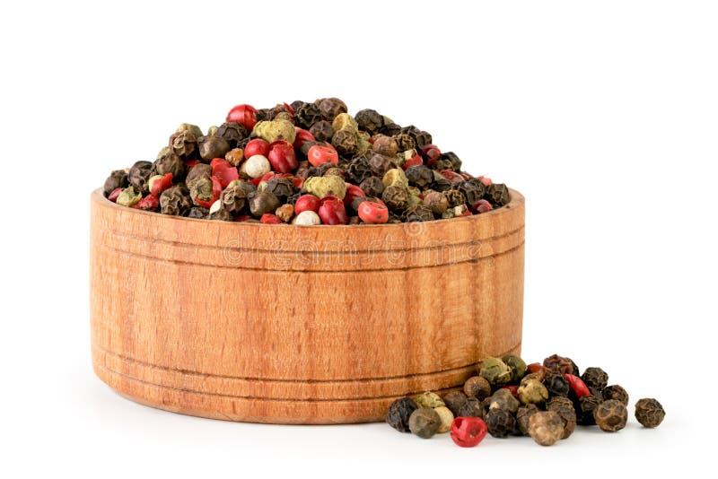 豌豆胡椒混合物在一块木板材的在白色 查出 免版税库存图片