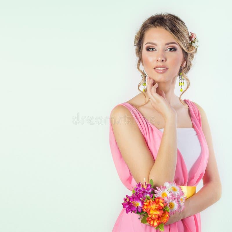 象一个新娘的美丽的妇女女孩有与花玫瑰的明亮的构成发型的在一件桃红色礼服的头 免版税库存照片