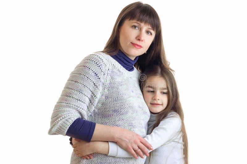 画象互相拥抱的逗人喜爱的年轻妈妈和女儿 免版税库存照片
