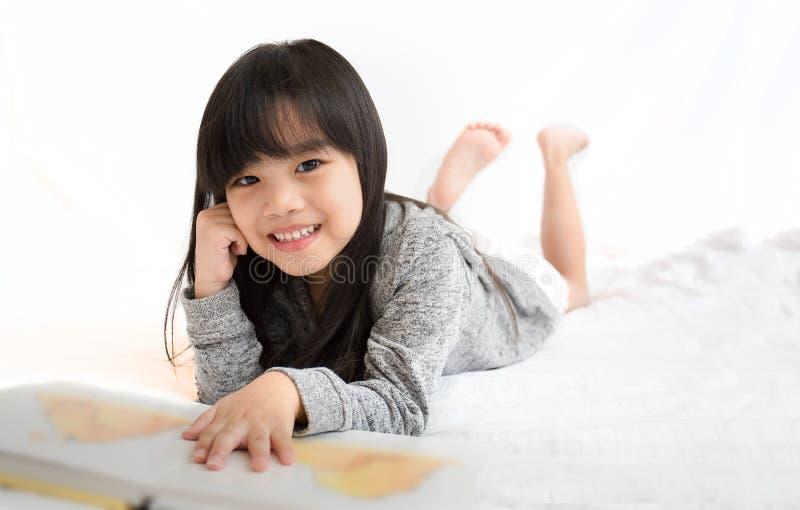 画象亚洲孩子、教育和学校概念-学生女孩阅读书 免版税库存图片